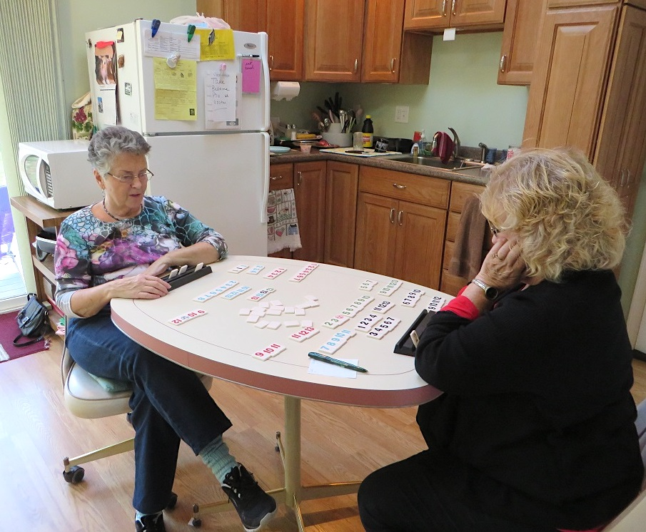 Simone and one of her caregivers, playing Rummikub.